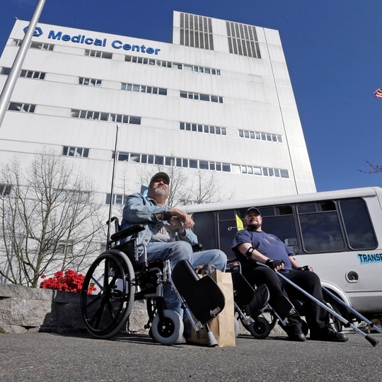 Veterans wait outside the Veterans Affairs Puget Sound Medical Center in Seattle on March 30, 2015. The site is one of 20 reopening for some compensation and pension exams in coming days. (Elaine Thompson/AP)