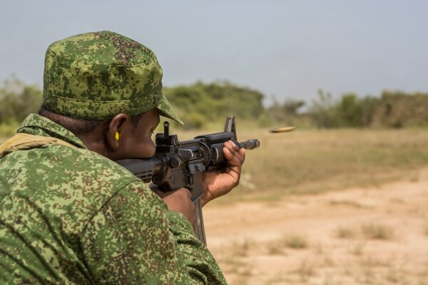 Belize Defense Force 2nd Lt. Herey Morgan, shoots an M4 Service Rifle while conducting rifle training at Hattieville Range, Belize, June 17, 2015. Tradewinds 2015 is a combined, joint U.S. Southern Command-Sponsored exercise and an opportunity for the participating partner nations to come together to enhance regional security. (U.S. Marine Corps Photo by Lance Cpl. Kimberly Aguirre/Released)