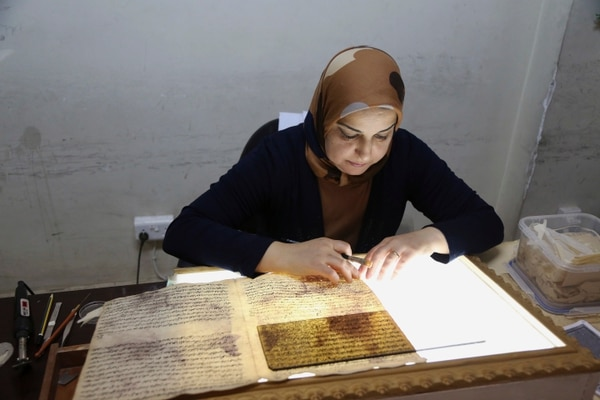 In this Tuesday, July 28, 2015 photo, a member of the library restoration staff works on a damaged document at the Baghdad National Library in Iraq. Librarians and academics in Baghdad are working to preserve what's left after thousands of documents were lost or damaged at the height of the U.S.-led invasion. As the Islamic State militants now set out to destroy Iraq's history and culture, a major preservation and digitization project is underway in the capital to safeguard a millennia worth of history. (AP Photo/Karim Kadim)