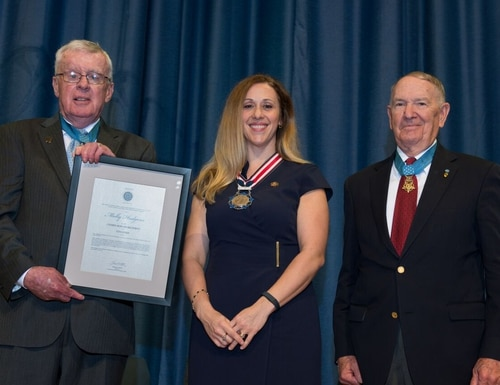 Molly Hudgens was selected for her courageous act on Sept 29, 2016, when she prevented a 14-year old middle school student from shooting teachers and students at Sycamore Middle School. Medal of Honor recipient Tom Kelley (left) and Walter Marm presented the Act of Courage Award. (Courtesy of the Congressional Medal of Honor Foundation)