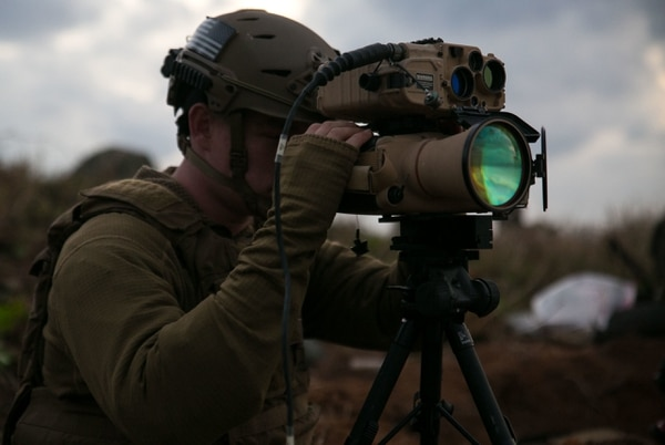 Marine Cpl. Craig Lewis, a communications chief with the 5th Air Naval Gunfire Liaison Company, uses two stacked devices, (on the top) the joint terminal attack controller laser targeting device and (on the bottom) the PAS-25, a thermal optic to see at night, Jan. 13 at Idesuna-Jima range W-174, Okinawa, Japan. (Cpl. Abbey Perria/Marine Corps)
