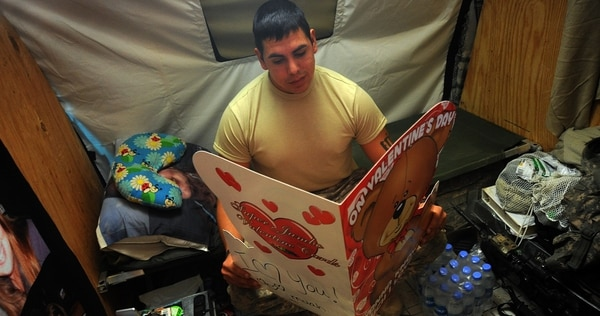 Army Staff Sgt. Pedro Chavez reads an over-sized Valentine's Day card from his wife while on Forward Operating Base Price in Helmand provice, Afghanistan, in 2012. (Staff Sgt. Christine Jones/Army)
