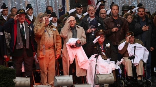 U.S. Battle of the Bulge veterans, front row, listen to the U.S. national anthem during a ceremony to commemorate the 75th anniversary of the Battle of the Bulge at the Mardasson Memorial in Bastogne, Belgium on Monday, Dec. 16, 2019. The number of aging veterans with complex service-connected disabilities is expected to grow, requiring the Department of Veterans Affairs to plan for their care. (Francisco Seco/AP)