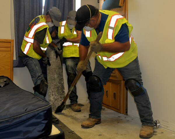 Personnel from the 502nd Civil Engineering Group remove carpet severely impacted by mold July 25-26. In addition to these efforts, personnel have placed dehumidifiers, replaced furniture and begun sanitizing rooms. (Capt. Alejandro Delgado/Air Force)