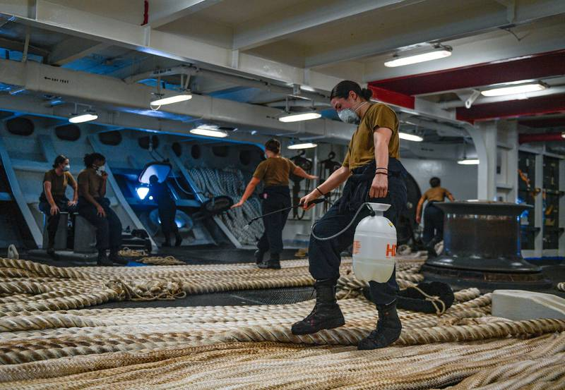 Boatswain's Mate Seaman Alexis Bias, assigned to the aircraft carrier USS Theodore Roosevelt (CVN 71), disinfects mooring line on May 21, 2020, following an extended visit to Guam in the midst of the COVID-19 global pandemic.