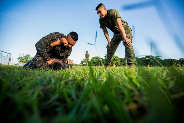 U.S. Marine Corps Capt. Juan Diaz, right, the officer in charge of Security Cooperation Team-Honduras, Special Purpose Marine Air-Ground Task Force-Southern Command monitors Honduran marines ground fighting while participating in the Honduran martial arts program at Naval Base Puerto Castilla, Honduras, Aug. 17, 2015. SCT-Honduras is currently deployed as part of the SPMAGTF-SC to assist the Centro de Adiestramiento Naval with implementing a training curriculum to create a Honduran marine Program. (U.S. Marine Corps Photo by Cpl. Katelyn Hunter/Released).