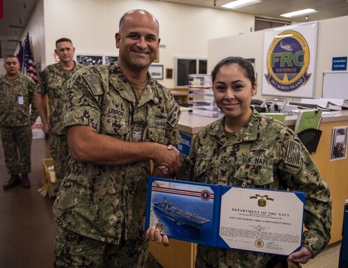 Capt. Rich Lebron, left, commanding officer of the amphibious assault ship Bonhomme Richard (LHD 6), awards former Air Traffic Controller 3rd Class Alize Acevedo the Navy and Marine Corps Achievement Medal in November 2019. (MC1 Benjamin Kittleson/Navy)