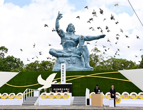Doves fly over the Statue of Peace during a ceremony at Nagasaki Peace Park in Nagasaki, southern Japan on Aug. 9, 2020, to mark the 75th anniversary of the world's second atomic bomb attack. (Kyodo News via AP)