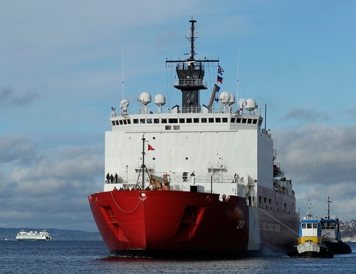 In this Nov. 30, 2018, file photo tugboats help the U.S. Coast Guard Cutter Healy icebreaker into her homeport of Seattle, as a Washington state ferry passes in the background following a four-month deployment to the Arctic Ocean. (Ted S. Warren/AP)