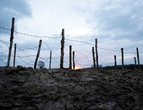 The sun rises behind barbed wire next to a reconstructed World War I trench in Ploegsteert, Belgium. Hundreds of troops died on the final morning of World War I, even after an armistice was reached and before it came into force. Death at the 11th hour highlighted the futility of a conflict that had become even more incomprehensible in four years of battle. (Virginia Mayo/The Associated Press)