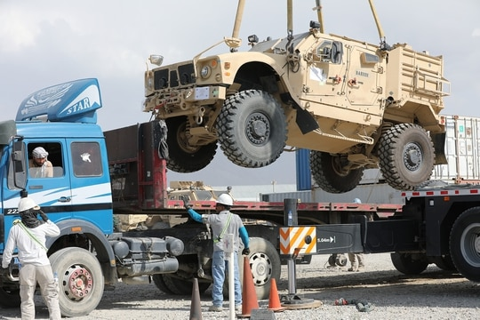 A Mine Resistant Ambush Protected vehicle is loaded on a flatbed trailer as part of the Army Field Support Battalion - Afghanistan, 10th Mountain Division Resolute Support Sustainment Brigade retrograde cargo operation on Bagram Air Field, Afghanistan, July 12, 2020. (Sgt. 1st Class Corey Vandiver/Army)