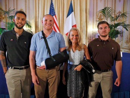 Anthony Sadler, a senior at Sacramento University in California, left, U.S. National Guardsman from Roseburg, Oregon, Alek Skarlatos, right, and U.S. Airman Spencer Stone, second from left, pose for photographers with Jane D. Hartley, U.S. Ambassador to France, before a press conference held at the U.S. Ambassador's residence in Paris, France, Sunday, Aug. 23, 2015. Sadler, Skarlatos and Stone helped foil a potentially deadly attack when they subdued a man armed with an assault rifle and other weapons on board a high-speed train bound for Paris two days ago. The man was known to intelligence services in three countries and had ties to radical Islam, authorities said Sunday. (AP Photo/Francois Mori)
