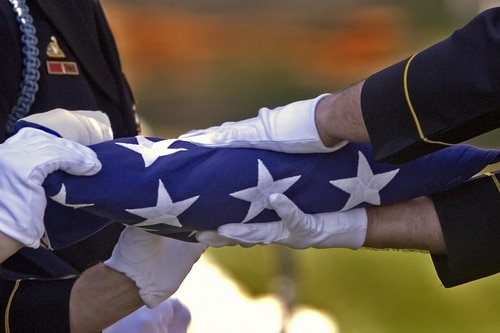 The Defense Department provides an American flag to drape the casket or to be presented at a memorial service. After the service, it is given to the next of kin. (Paul J. Richards/AFP/Getty Images)