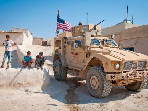 Children gather around a U.S. tactical vehicle during a patrol along the demarcation line outside Manbij, Syria, July 14. (Staff Sgt. Timothy R. Koster/Army)