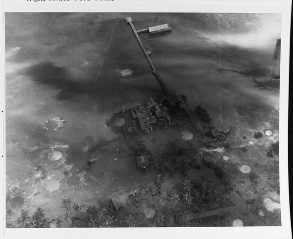 Wrecked facilities on Butaritari Island, Makin Atoll, on 20 November 1943, following the pre-invasion bombardment. This photo was from a spotter plane for the cruiser Minneapolis. On Chong's wharf is in center background, with bomb craters and wrecked buildings nearby. Note trucks by their garage in lower center. (National Archives)