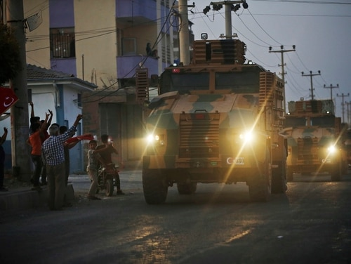 Shortly after the Turkish operation inside Syria had started, local residents cheer and applaud as a convoy of Turkish forces vehicles is driven through the town of Akcakale, Sanliurfa province, southeastern Turkey, at the border between Turkey and Syria, Wednesday, Oct. 9, 2019. (Lefteris Pitarakis/AP)