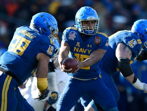 In this Dec. 28, 2017, file photo Navy quarterback Malcolm Perry hands off to Anthony Gargiulo against Virginia in the first half of the Military Bowl NCAA college football game in Annapolis, Md. Navy is handing the keys to its triple-option offense to Perry, who was the starting slotback for eight games last season before coach Ken Niumatalolo switched him to quarterback to spark a struggling offense. (Gail Burton/AP)