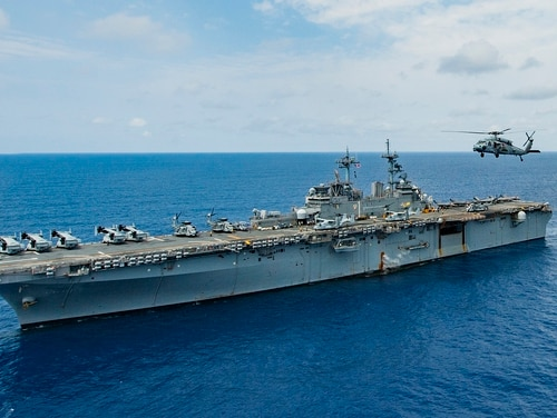 An MH-60S Sea Hawk helicopter flies alongside the amphibious assault ship USS Wasp (LHD 1) on March 20, 2018, in the Philippine Sea. (MC3 Taylor King/Navy)