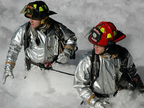 Lt. Shayne Carder and Staff Sgt. Bradley McCroskey, 20th Civil Engineer Squadron firefighters, work their way through the foam in Hangar 1200 Jan. 17. the fire supression system in the Hangar was activated Jan. 17. (Courtesy photo)