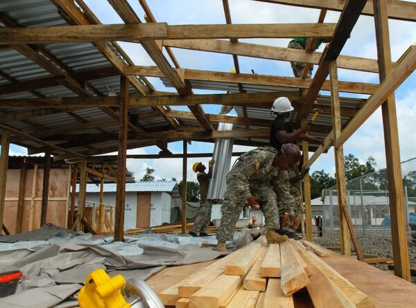 Spc. Quondeshia Butler, center, Soldier of the 104th Engineer Company, 62nd Engineer Battalion, 36th Engineer Brigade, works with Armed Forces of Liberia soldiers Pfc. Sammy Joseph, left, and Cpl. Matthew Cooper, of the 1st Engineer Company, 23rd Infantry Brigade, construct a building for the Ebola treatment unit site in Sinje, Liberia, Nov. 14, 2014. Butler, Joseph and Cooper all stated that they enjoyed working together and have learned a lot from each other in the process. Operation United Assistance is a Department of Defense operation in Liberia to provide logistics, training and engineering support to U.S. Agency for International Development-led efforts to contain the Ebola virus outbreak in western Africa. (U.S. Army photo by Spc. Caitlyn Byrne, 27th Public Affairs Detachment/Released)