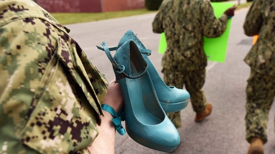 """A sailor from Navy Expeditionary Combat Command carries a pair of shoes, painted teal to symbolize victims of sexual assault, as she participates in the Aug. 25 """"Walk a Mile in Their Shoes"""" command event at Joint Expeditionary Base Little Creek. (Mass Communication Specialist 3rd Class Lisa Reese/Navy)"""