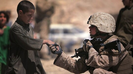 A female Marine sergeant, I Marine Expeditionary Force, shakes hands with an Afghan child during a mission in Helmand province, Afghanistan. (Sgt. Michele Watson/Marine Corps)