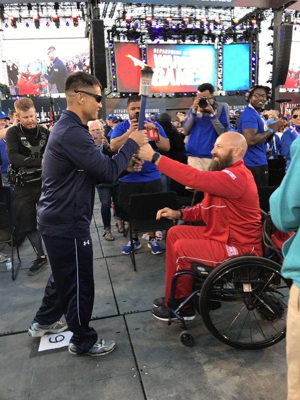 Marine Corps Gunnery Sgt. Douglas Godfrey, right, hands the torch to Coast Guard Lt. Daniel Lee during the opening ceremonies for the 2018 Warrior Games at the Air Force Academy in Colorado Springs, Colo., June 2, 2018. (Stephen Losey/Staff)