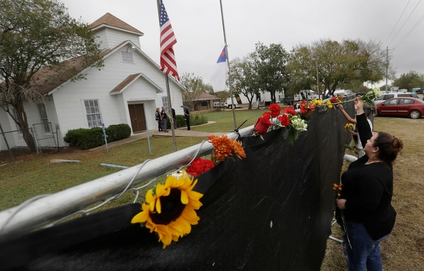 Rachel Vasquez places flowers in a fence for the victims of a shooting outside of the Sutherland Springs Baptist Church in Texas Nov. 12. Congress is moving to specifically add domestic violence to the list of crimes under the Uniform Code of military Justice. (Eric Gay/AP)