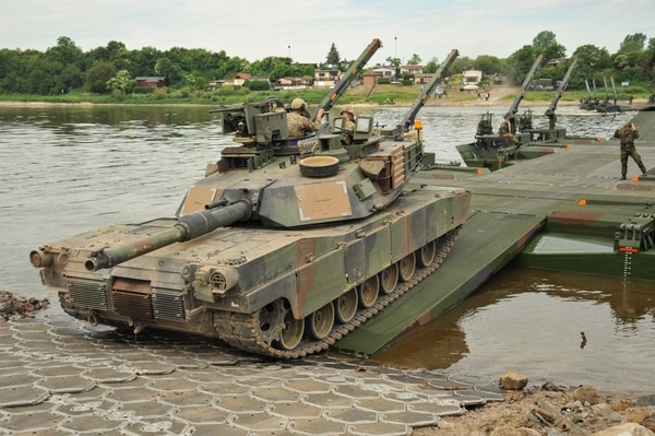 """U.S. Army M1A2 SEP V2 Abrams Main Battle Tanks, M2A3 Bradley Infantry Fighting Vehicles as well as various trucks and vehicles of Delta Company """"Dark Knights"""", 3rd Battalion, 69th Armor Regiment, 1st Armor Brigade Combat Team, 3rd U.S. Infantry Division conduct combined assault river crossing operations at the river Elbe with German Army M3 amphibious bridging vehicles during exercise Heidesturm Shock near Storkau, Germany, June 06, 2015. (U.S. Army photo by Visual Information Specialist Markus Rauchenberger/released)"""