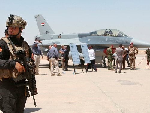 A member of the Iraqi SWAT team stands guard as security forces and others gather next to a U.S.- made F-16 fighter jet on July 20, 2015, during the delivery ceremony at Balad air base, Iraq. (Khalid Mohammed/AP)