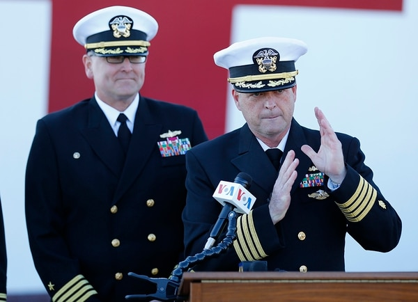 Capt. Kevin Buckley, commanding officer for the USNS Comfort, gestures as he speaks to the media as Capt. William Shafley III, left, looks on as the Navy hospital ship USNS Comfort arrives at Naval Station Norfolk, Tuesday, Dec. 18, 2018, in Norfolk , Va., after an 11-week medical support mission to South and Central America. The ship treated over 26,000 patients and conducted approximately 600 surgeries. (Steve Helber/AP)