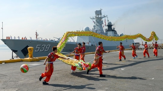 Dragon dancers perform as Chinese guided-missile frigate Wuhu prepares to dock at the international port in Manila on January 17, 2019. - A Chinese naval task group, consisting of two frigates -- the Wuhu 539 and Handan 579 -- and a replenishment ship Dongpinghu (960) arrived at Manila's international port for a four-day goodwill visit. (TED ALJIBE/AFP/Getty Images)