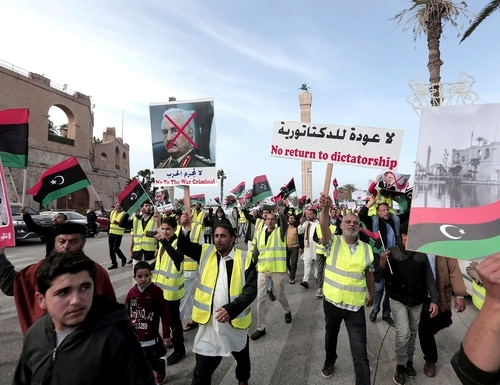 In this April 19, 2019, file photo, protesters wear yellow vests at a protest as they wave national flags and chant slogans against Libya's Field Marshal Khalifa Hifter, in Tripoli, Libya. (Hazem Ahmed/AP)