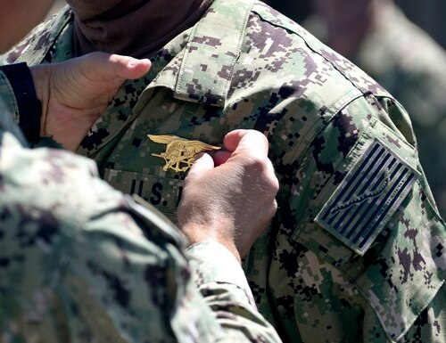 Cmdr. Keith Marinics, commanding officer of Naval Special Warfare (NSW) Basic Training Command, places a special warfare (SEAL) pin, known as a Trident, on a member of SEAL Qualification Training Class 336 during a graduation ceremony at NSW Center in Coronado, Calif., April 15, 2020. (Mass Communication Specialist 1st Class Anthony W. Walker/Navy)
