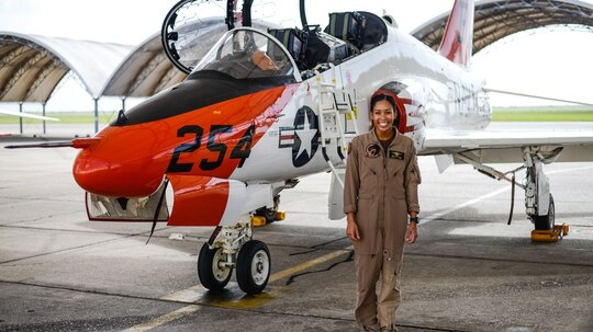 Student Naval Aviator Lt. j.g. Madeline Swegle, assigned to the Redhawks of Training Squadron 21 at Naval Air Station Kingsville, Texas, stands by a T-45C Goshawk training aircraft following her final flight to complete the undergraduate Tactical Air (Strike) pilot training syllabus July 7. Swegle is the Navy's first known Black female strike aviator and will receive her gold wings during a ceremony July 31. (Lt. j.g. Luke Redito/Navy)