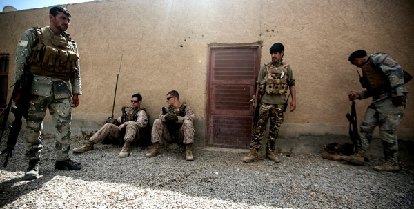 Marines with Task Force Southwest (TFSW) and policemen with the 505th Zone Afghan National Police stage after a movement to 6th Sub District Headquarters in Bost Kalay, Afghanistan, March 17, 2018. (Sgt. Sean J. Berry/Marine Corps)