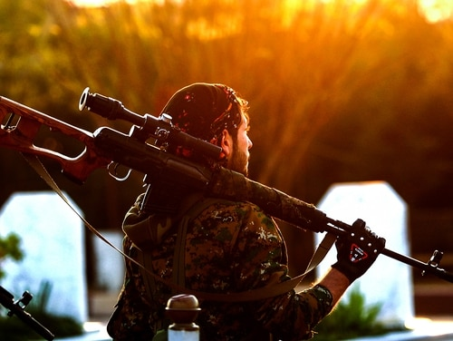 A Syrian Democratic Forces (SDF) fighter holds a sniper rifle on his shoulder as he attends the funeral of a slain Kurdish commander in the northeastern city of Qamishli on Dec. 6, 2018. (Delil Souleiman/AFP via Getty Images)