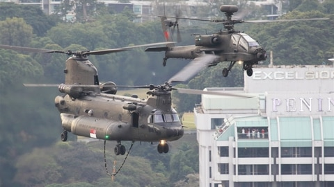 An upgraded Republic of Singapore Air Force Boeing CH-47SD Chinook flies in formation with an AH-64D Apache over Singapore's Central Business District during the country's annual National Day Parade on the 9th of August. (Mike Yeo/Staff)
