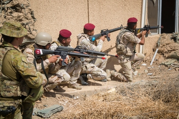 Iraqi soldiers attending a train-the-trainer course prepare to clear a building during urban operation training at the Iraqi Army Noncommissioned Officer Academy at Camp Taji, Iraq, Sept. 30, 2015. The soldiers learned how to properly clear a building of threats through multiple types of entry points. This training is instrumental to the success of the Iraqi security forces in reclaiming territory occupied by the Islamic State of Iraq and the Levant in urban locations. (U.S. Army photo by Spc. William Marlow/Released)