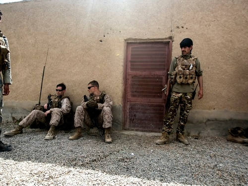 Marines with Task Force Southwest and policemen with the 505th Zone Afghan National Police stage after a movement to 6th Sub District Headquarters in Bost Kalay, Afghanistan, March 17. (Sgt. Sean J. Berry/Marine Corps)