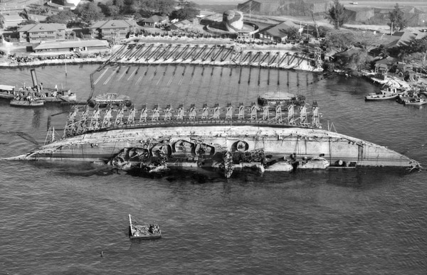 An aerial view of salvage operations on the USS Oklahoma at Pearl Harbor, Hawaii. The ship capsized during the Japanese attack on Pearl Harbor in 1941. (U.S. Navy)