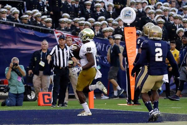 Notre Dame running back Dexter Williams, center, scores a touchdown against Navy Saturday in San Diego. (Gregory Bull/AP)