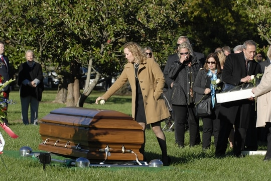 After a graveside ceremony, Michelle Black places a white rose on top of Bryan Black's casket and says goodbye for the last time. (Rich LaSalle/Courtesy photo)