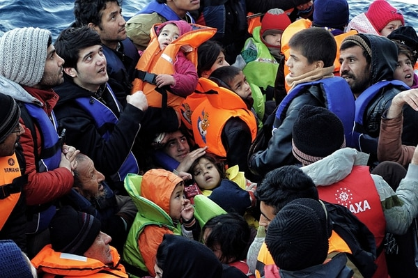 A picture taken on February 20, 2016 shows children among refugees and migrants on a rubber boat on their way from Turkey to the Greek northern island of Lesbos as Greek coast guards embark on the boat off Mytilene, Lesbos. / AFP / STRINGER (Photo credit should read STRINGER/AFP/Getty Images)