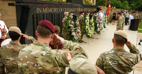 Soldiers salute as taps play at the U.S. Army Special Operations Command Fallen Special Operations Soldier Memorial ceremony on Fort Bragg, N.C. The names of four soldiers killed in last year's Niger ambush were among those that have been added to the memorial wall. (Andrew Craft /The Fayetteville Observer via AP)