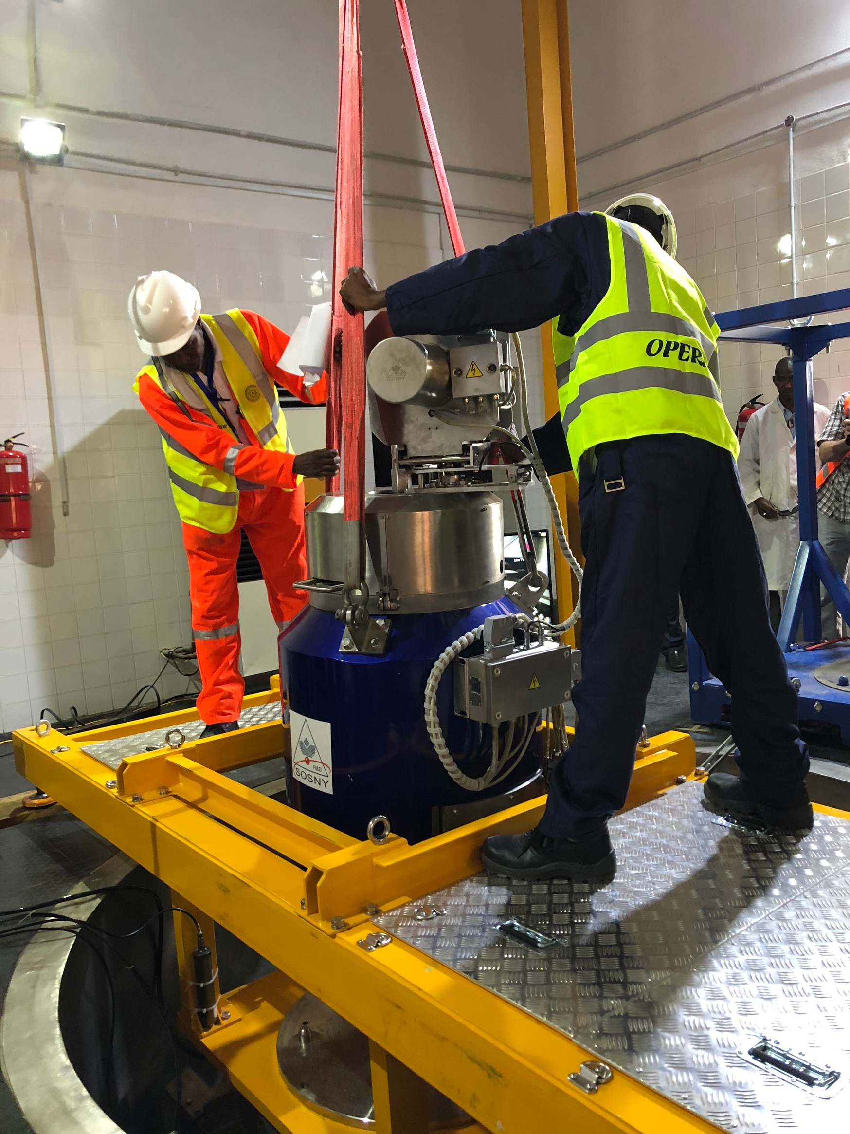 Technical experts from Nigeria's Centre for Energy Research and Training stand over the miniature neutron source reactor and prepare to load the HEU reactor core into an interim transfer cask. (U.S. National Nuclear Security Administration)