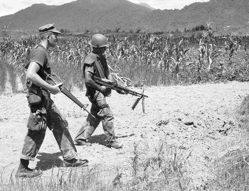 A pair of U.S. Marines patrol a free-fire zone in Da Nang, near the Vietnamese border with Laos, on July 21, 1970. (Mark Godfrey/AP)