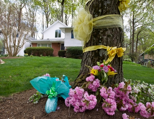 Flowers and ribbons adorn a tree outside the Weinstein familyhouse in Rockville, Md., Thursday, April 23, 2015. Earlier, President Barack Obama took full responsibility for the counterterror missions and offered his