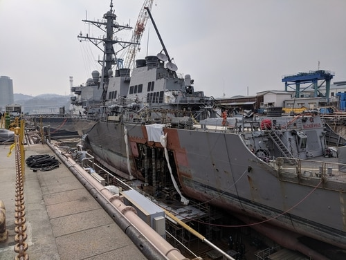 The destroyer John S. McCain sits in dry dock as crews work to rebuild the section damaged in the August collision. A chief was sentenced today for his role in certifying sailors who were ultimately unqualified to perform basic ship-steering operations. (Photo by David B. Larter, Staff)