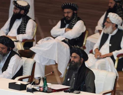 In this Sept. 12, 2020, file photo, Taliban co-founder Mullah Abdul Ghani Baradar, bottom right, speaks at the opening session of peace talks between the Afghan government and the Taliban in Doha, Qatar. (Hussein Sayed/AP)